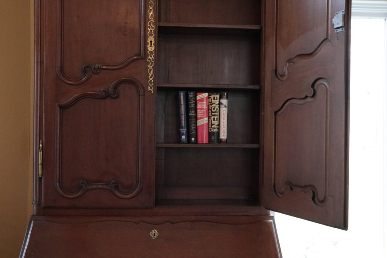Monumental Old World Charmer mahogany Don Rousseau monumental Louis XV secretary. Hand carved details, brass handles, pulls and escutcheons. Four deep and long shelves - three fabulously designed drawers with tons of storage. Old World Charm.