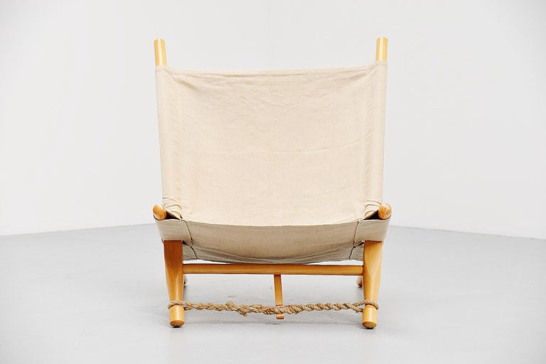 Very nice dynamic low lounge chair designed by Ole Gjerløv-Knudsen, manufactured by Cado, Denmark, 1958. The chair has a birch wooden frame existing in 4 parts sliding in each other to change the angle if wanted. The canvas seat and the rope