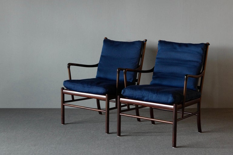 "A stunning matching pair of ""Colonial"" armchairs by Ole Wanscher for P Jepperson. They have a mahogany frame and a woven rattan cane seat. The cushions on the seat and back are upholstered in blue wool. These chairs are elegant and refined in"