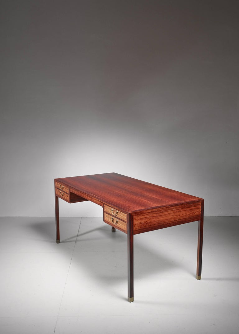 A large freestanding desk, by Danish designer Ole Wanscher and produced by A. J. Iversen. The desk has four drawers with brass handles and the legs have brass socks.