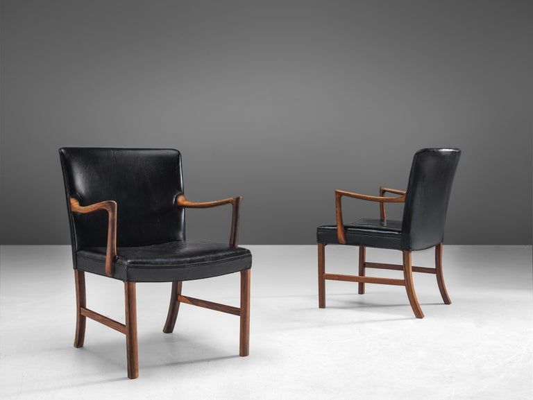 Ole Wanscher for A. J. Iversen, pair of armchairs, rosewood, leather, Denmark, 1940  This pair of elegant easy chairs in black leather and rosewood are designed by the Danish designer Ole Wanscher. The chairs are wide and highly comfortable. The