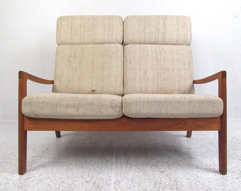 This teak high-back two-seat sofa was designed by Ole Wanscher as part of his 'Senator' line, circa 1960s. Please confirm item location (NY or NJ) with dealer.