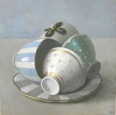 """Elegant Still Life of White, Gold, Blue, and Green Cups on a Plate"""