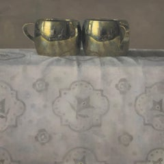 """""""Elegant Still Life of Two Gold Metal Cups on Patterned Fabric"""""""