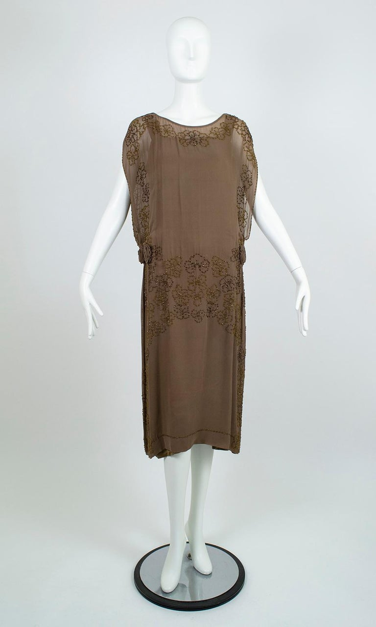 From the estate of department store heiress Estela Jácome, this exceptional early 20s dress is the epitome of alluring modesty. Despite its sensual hip rosettes, high-split tabard sides and deep arm holes, the wearer remains fully covered thanks to