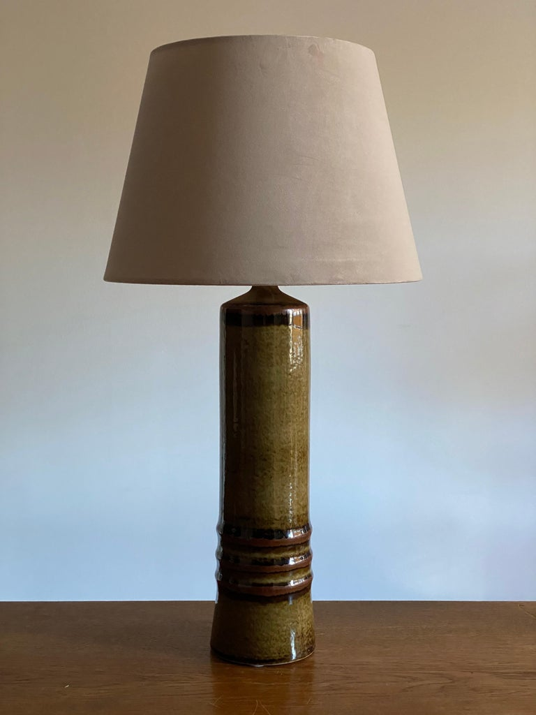 A large and sculptural table lamp, designed by Olle Alberius and produced by Rörstrand. Marked. Features a sculptural form and a highly artistic green / black / brown glaze.   Lampshade attached is for illustration, the lamp is offered without a