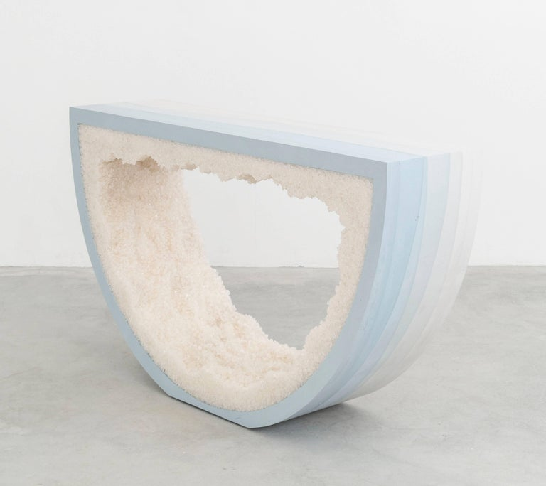 Composed from a combination of materials, the semicircle console consists of a hand-dyed white cement exterior and a rock salt interior. Packed by hand within the smooth ombre of sky blue cement, the white rock salt forms an organic texture to