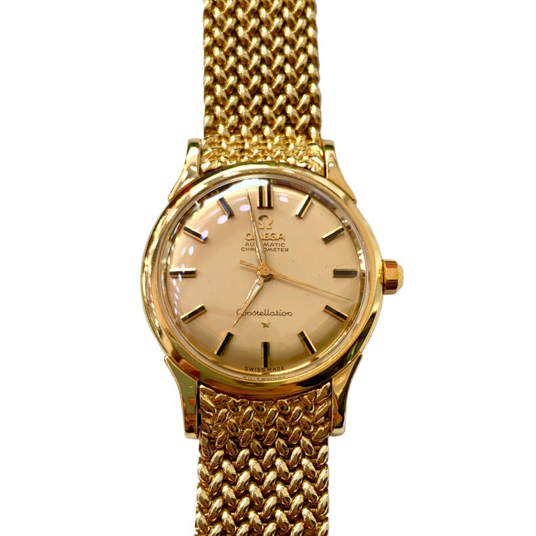 Men's very heavy 18K yellow gold Omega Constellation automatic chronometer watch circa 1960's. It has a very flexible permanent mesh bracelet, movement #505, case #2852-2853 and serial numbers 11462243. The entire piece weighs 127 grams! The