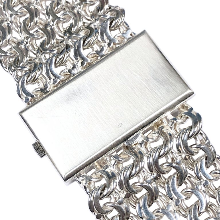 Circa 1970 Omega De Ville Bracelet Watch, Sterling Silver 2 piece Case measuring 1 1/2 X 3/4 inch, attached sterling Silver very soft and flexible link bracelet measuring 1 1/4 inch wide. Total watch length 7 1/2 inches. 17 Jewel Mechanical, Manual