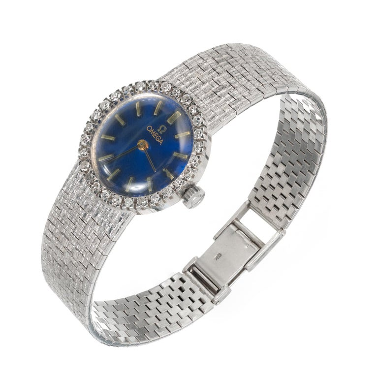 Vintage 1960's ladies Omega wristwatch in 18k white gold with diamond bezel and mesh textured band. Refinished royal blue Omega dial. 17 Jewel 620 Omega manual wind 17 jewel movement   28 single cut diamonds 1.2-1.5mm approx total weight: .35cts