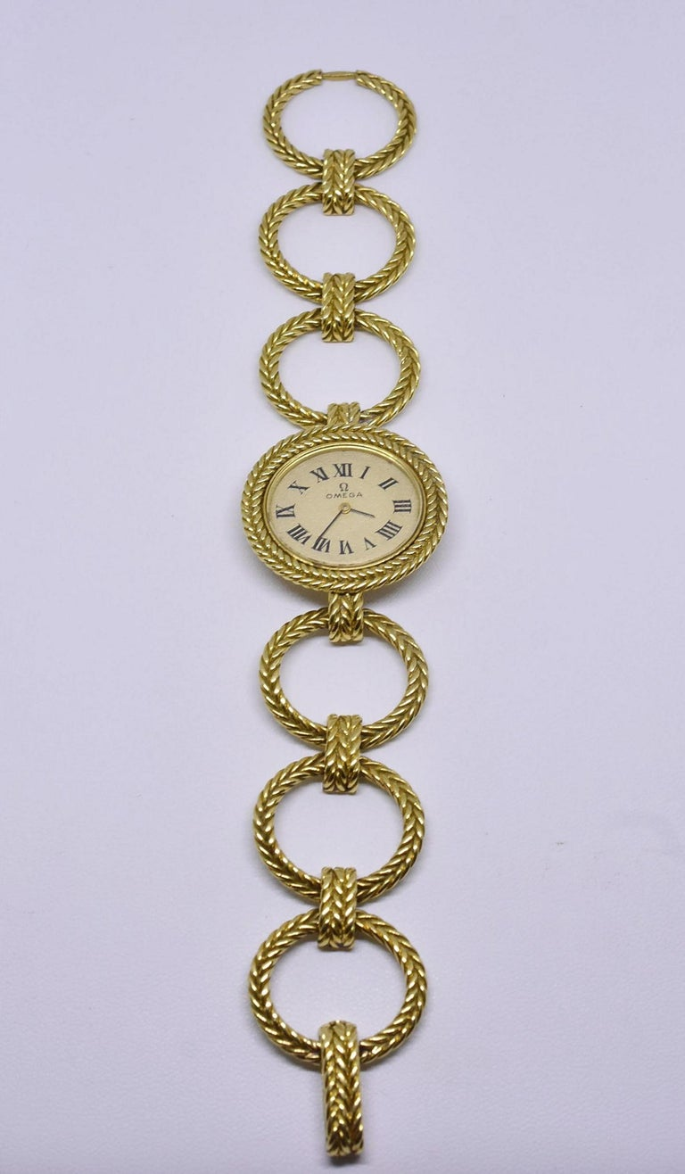 Beautiful ladies Omega 18-karat winding gold watch. This is an unusual watch with oval braided gold links making a bracelet. The dial is in excellent shape, the crystal has slight scratching due to age and use. Measures: 6 1/2