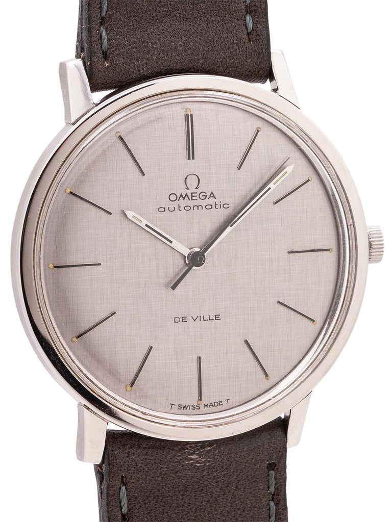 Very dressy mid century design vintage man's Omega stainless steel De Ville ref # 165.008 circa 1968. Featuring a sleek and slim 35 x 38mm case with screw down case back, acrylic crystal, and original finely linen textured matte silver dial with