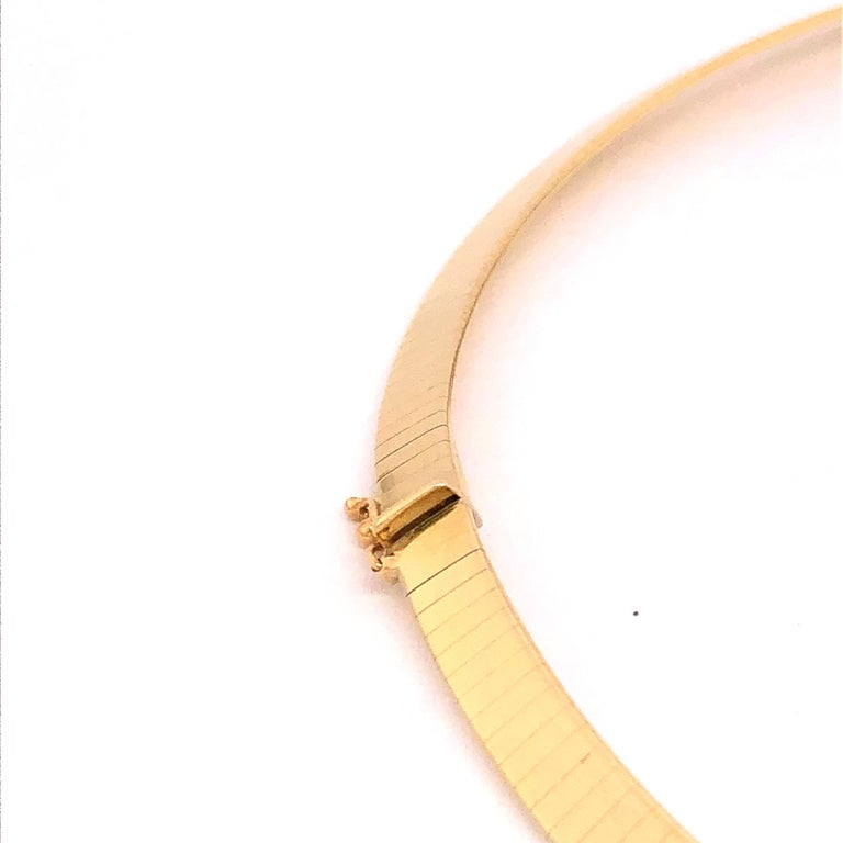 Elegantly bold this omega style 14K yellow gold necklace is well suited for casual and business occasions. It sits comfortably on your collar almost becoming a part of you.   Stamped: Italy, 14Kt