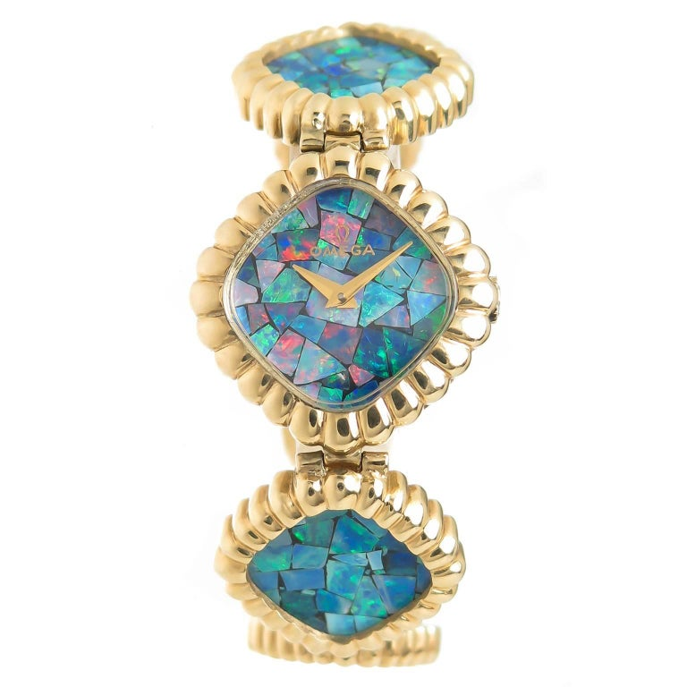 Circa 1980 Omega ladies 14k Yellow Gold Bracelet watch, measuring 7 1/8 inch in length and 7/8 inch wide and having scalloped borders. Each individually linked sectioned of the bracelet is set with a bright Fire Opal Mosaic as is the Face of the