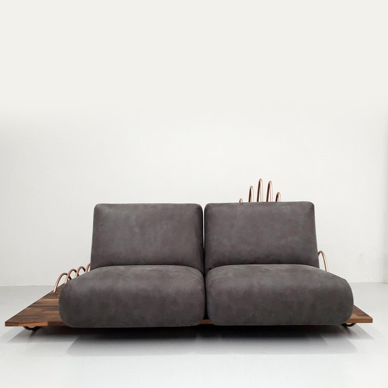 This convertible sofa can be transformed into a table by placing its wooden base atop the folded down seats. Its backrest can be used as a magazine stand, making it perfect for residential use or in a hotel or reception area. Its base is in solid