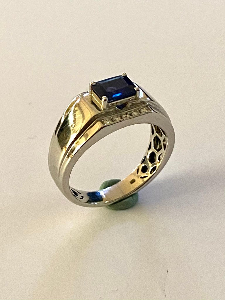 One (1) 18k. White Gold Sapphire & Diamond Ring. 1 Natural Corundum, Sapphire, Emerald, step cut  = 6.6 x 5.3 x 2.7 mm  = 1.00 Carat  (indications of heating present) 10 natural Diamonds, round Brillilant = 0.15 ct (total)  VSI - SI  F-G Total