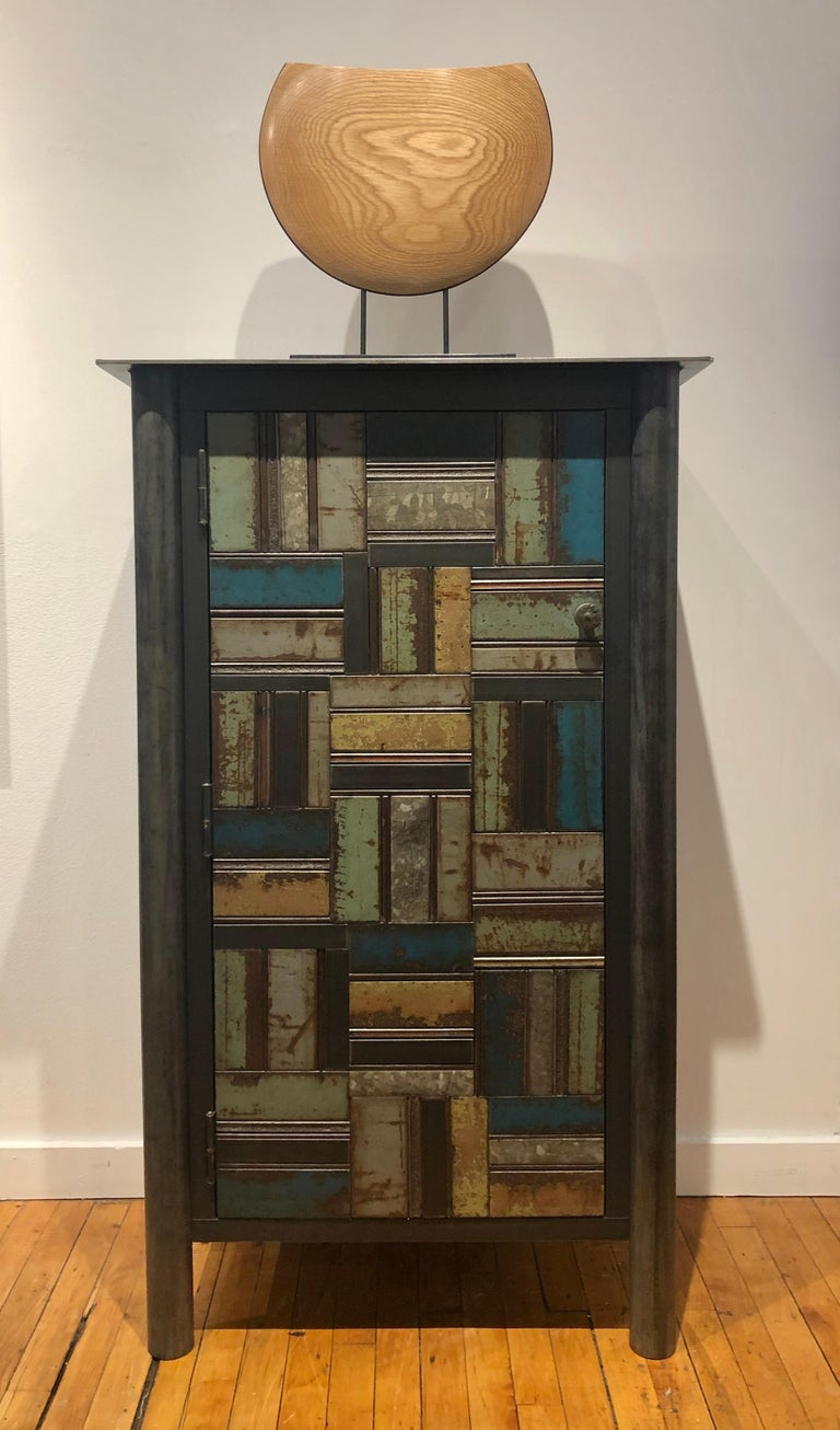 This is a totally functional one door cupboard. It is created from hot rolled steel and found steel. The legs are made from salvaged pipe. The panels on the door fronts and sides are made from salvaged pieces of steel with the original paint and