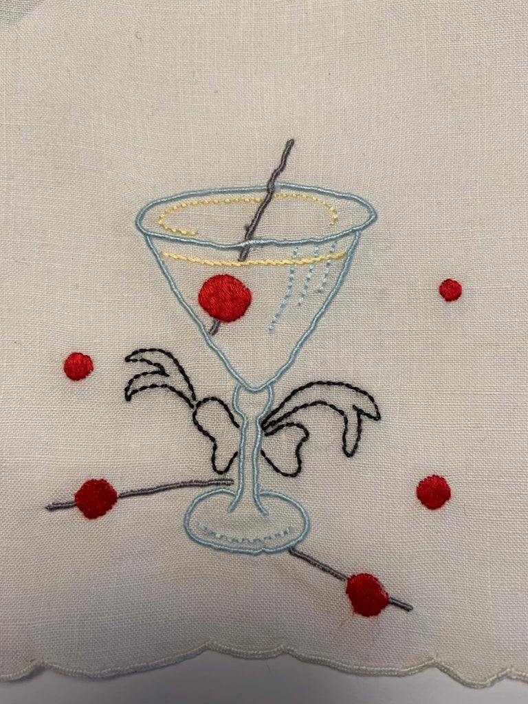 A sleek stemmed Manhattan cocktail glass is embroidered in blue with a red cherry and grey stirrer inside on this set of twelve white cocktail napkins. They have embroidered red dots adding to the festive look and they are all linen with scalloped