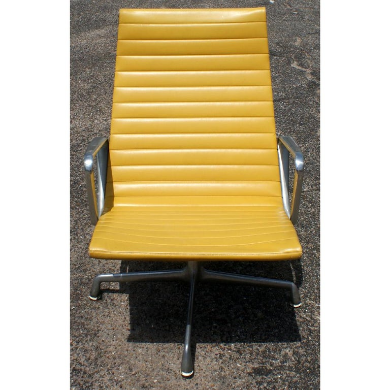 One Mid-Century Modern lounge chair designed by Charles and Ray Eames and made by Herman Miller. Extruded aluminum frame on four-star swivel base with yellow vinyl upholstery.