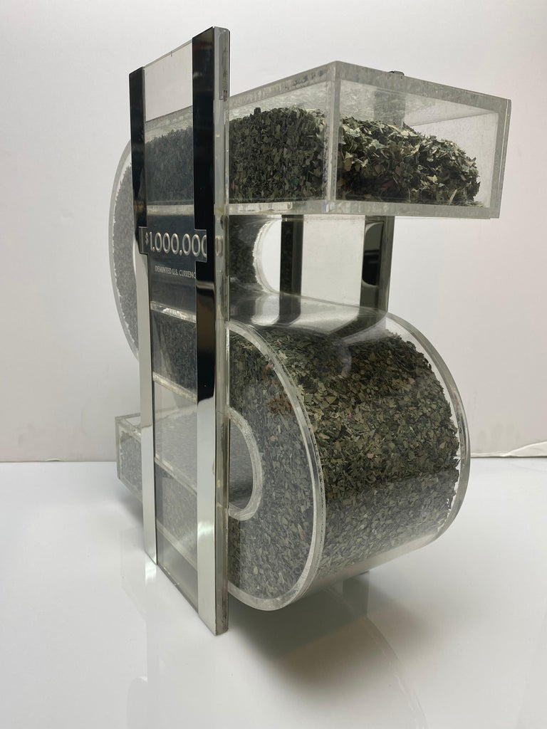 A fantastic object. A figural Lucite dollar sign filled with $1,000,000 of shredded currency. The front and back strikes are both covered in nickel. A fun and outrageous object for any room in the home.