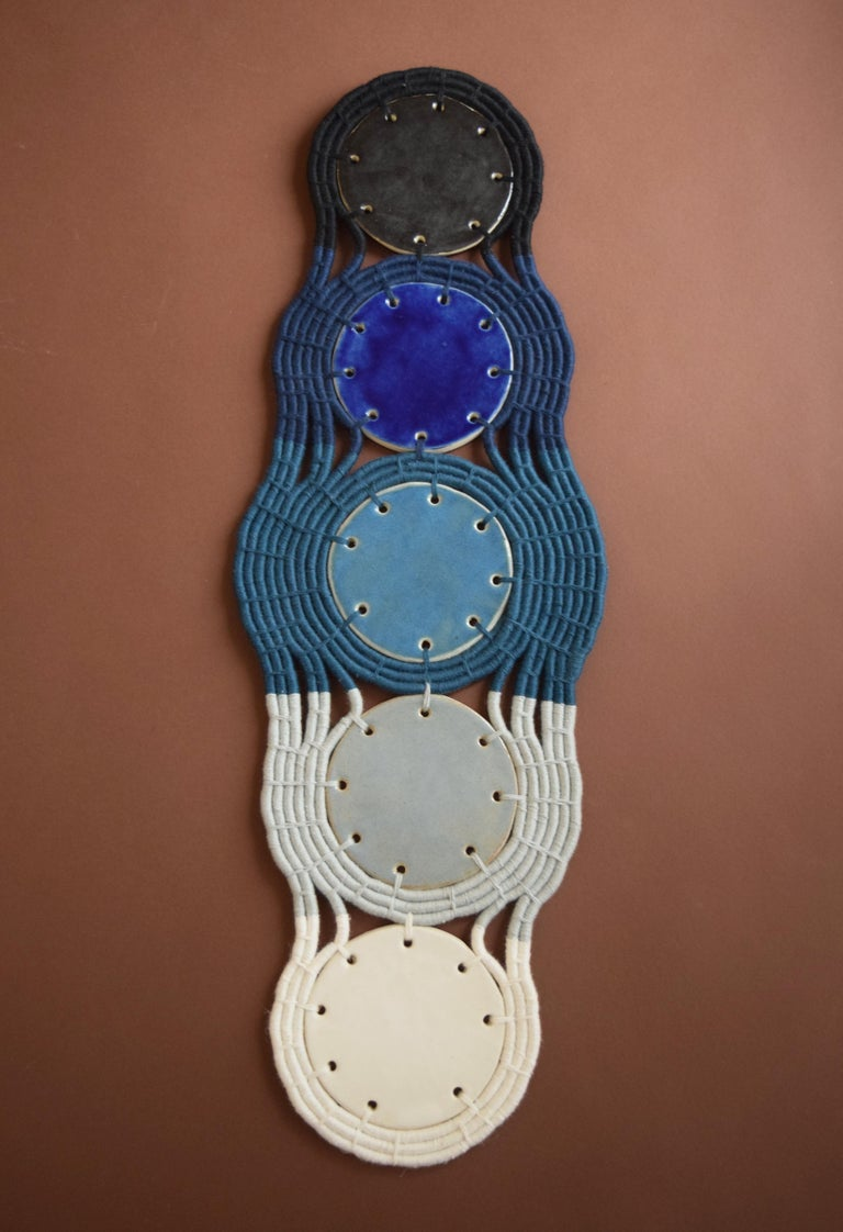 One of a kind wall sculpture #715 by Karen Gayle Tinney  One of a kind wall sculpture in ceramic and woven cotton. Handmade ceramic discs glazed in shades of blue, black, and white. The ceramic pieces are linked together using a coiling technique