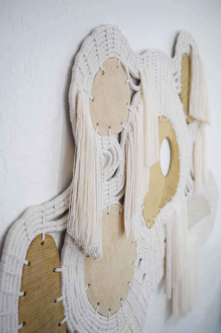 One of a kind wall sculpture #674 by Karen Gayle Tinney  One of a kind wall sculpture in ceramic and woven cotton. Handmade ceramic shapes are left unglazed with scored texture to create a variety of surfaces. The ceramic pieces are linked