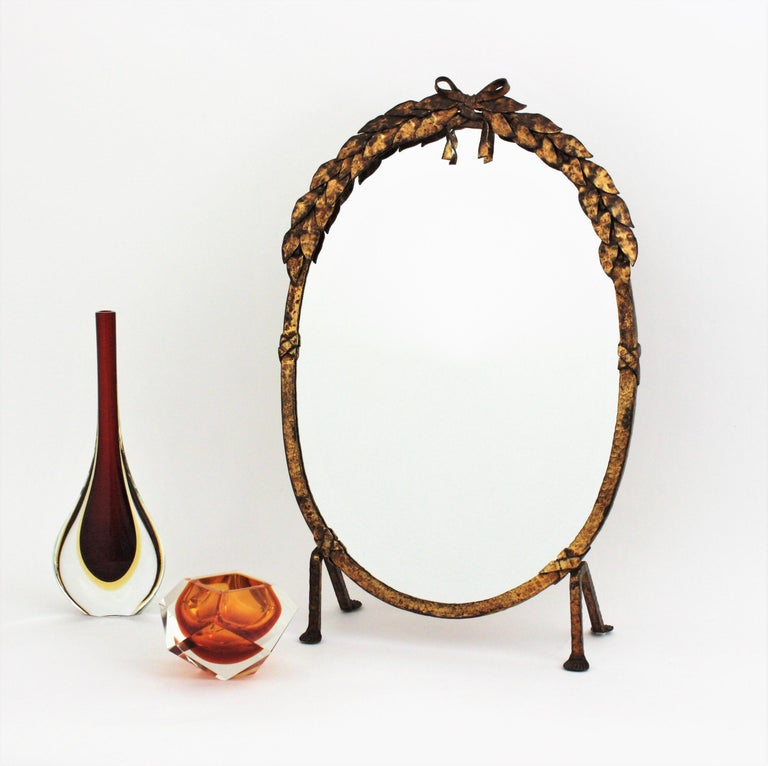 Stunning hand wrought iron oval table / vanity mirror or standing mirror with foliage details, France, 1940s. This lovely oval mirror is all made by hand in iron. It stands up on four iron legs. The frame is heavily adorned by the hammer marks and