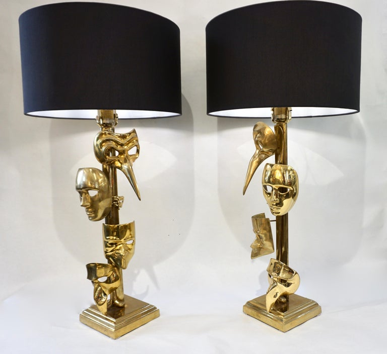 Vintage Italian pair of very rare lamps, handcrafted in cast bronze, extraordinarily decorated with carnival masks in different sizes and each different from the other, on a square stepped bronze base.