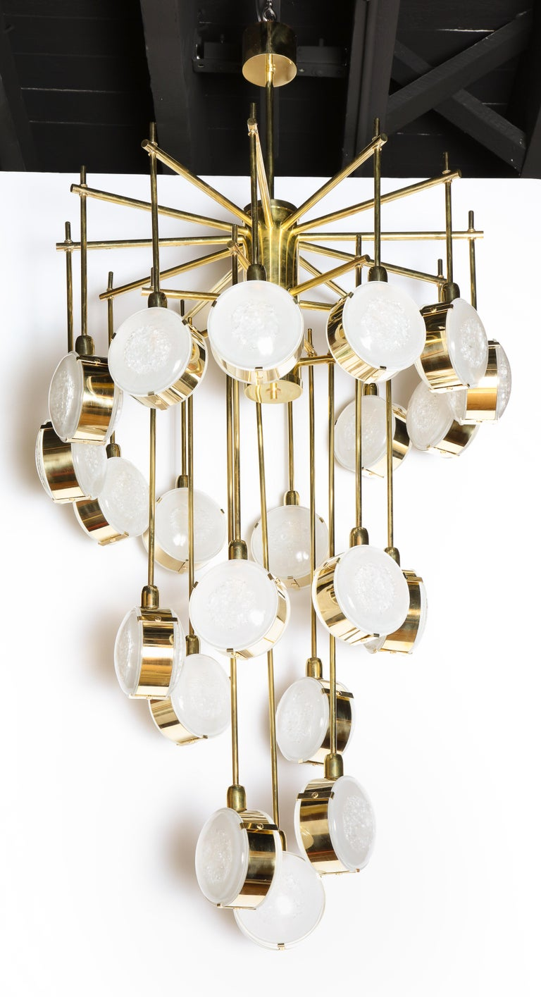 Unique in its design, this cascading chandelier is made of solid natural brass rods that turn and cascade like a spiral staircase. Double sided texture opaque Murano glass globes or discs are attached at the end of each rod. Inside each globe or