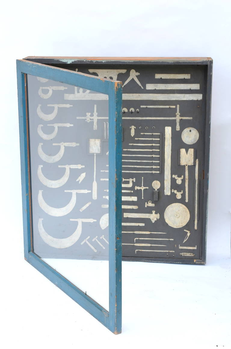 Unique mechanic's tool cabinet, closed with a glass door and hand painted tool shaped with hooks. Can be used as a display case for actual tools or just