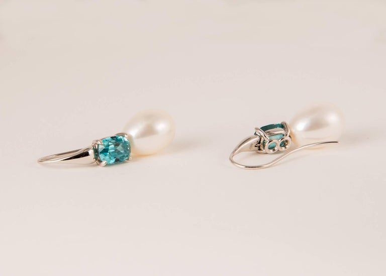 Handmade 18k white gold earrings featuring a matched pair of fiery blue zircons and a pair of cultured freshwater pearls. Simply elegant !!! 1 1/4 inches in length