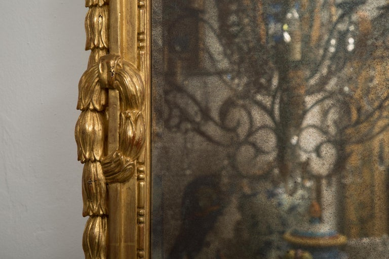 This is a stately carved Italian giltwood mirror. Each mirror has a cornice with central urn with flowers flanked by two prominent cornucopia over a mirror plate framed by ornately carved gilt frame, 20th century.