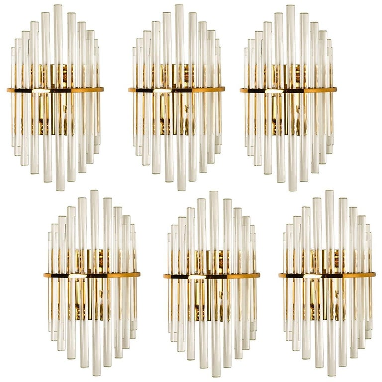 Clean lines to complement all decors. Wonderful high-end wall lights for Lightolier. With brass detail and hanging waterfall glass giving each piece an elegant appearance which refracts the light, filling a room with a soft, warm glow.  The wall