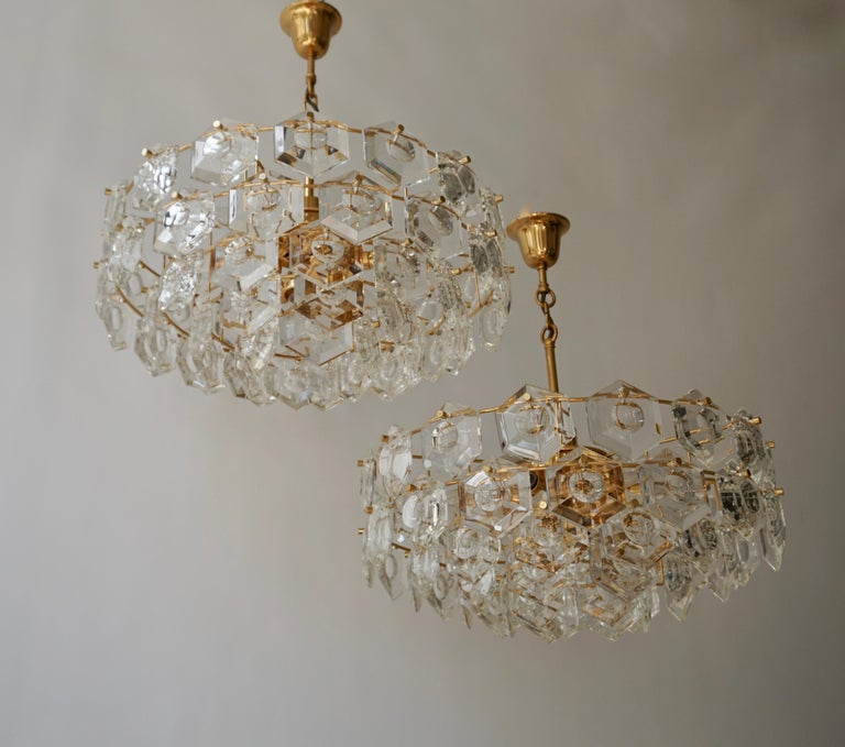 Two chandeliers with sculptural faceted crystals on a gold-plated brass frame made by Kinkeldey, Germany in the 1960s. The lamp takes one large and six small Edison base bulbs. Very good condition.  Measures: Diameter 52 cm. Height fixture 23