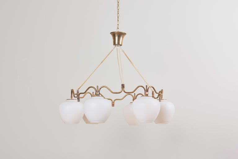 A round brass chandelier with six opaline glass shades, by Bent Karlby for Lyfa. The brass shows a beautiful patina.  To be on the safe side, the lamp should be checked locally by a specialist concerning local requirements.