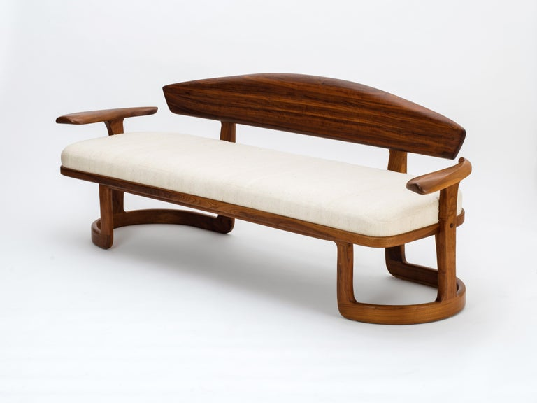An exceptional American Studio sofa executed in black walnut and finished with a seat cushion upholstered in raw silk, designed and built by Larry and Nancy Buechley, circa 1987. This highly sculptural form comprises a bent-laminated base that