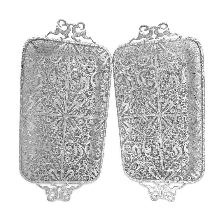 This beautiful pair has been made by hand and it is absolutely nice and pretty. The trays are persian silver filigree 0.99 karat which is almost pure silver . The handles are well designed with two goats on each side . The trays has four stands