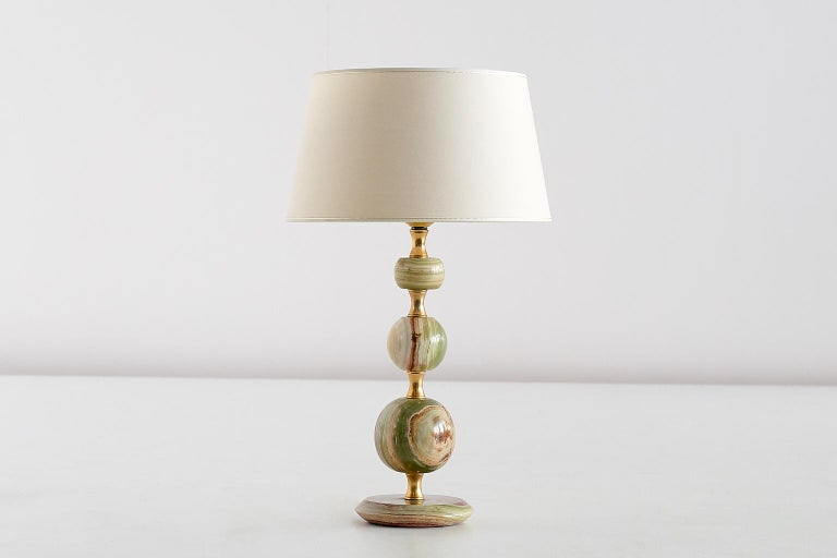 This elegant table lamp was produced in Italy in the late 1970s. The stacked base consists of three onyx spheres and four brass rings, resting on a circular onyx foot. The contrasting veins of the red, white and green onyx give the lamp a refined