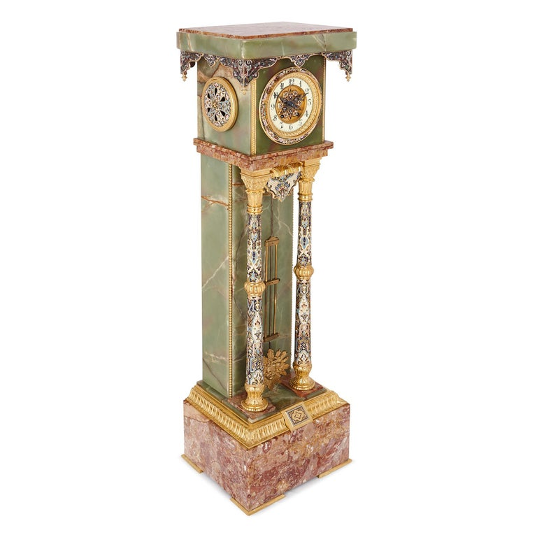This colorful longcase clock was created in France in the late 19th Century. It has been crafted from marble and onyx, and decorated with gilt bronze and champlevé enamel. Onyx was a popular crafts material in antiquity, but was forgotten about in