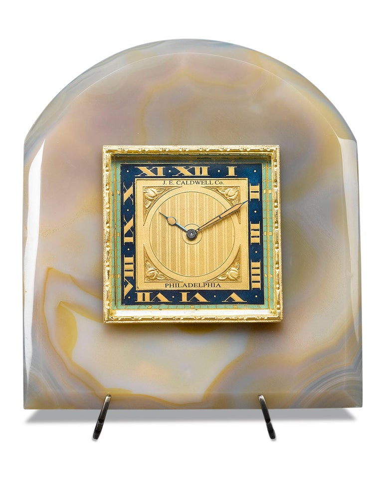 The Art Deco style is beautifully executed in this enchanting desk clock by J.E. Caldwell. The gilded dial, beautifully enameled in midnight blue and celadon green, sports four perfect apples in relief at its corners, and is framed by a luxurious