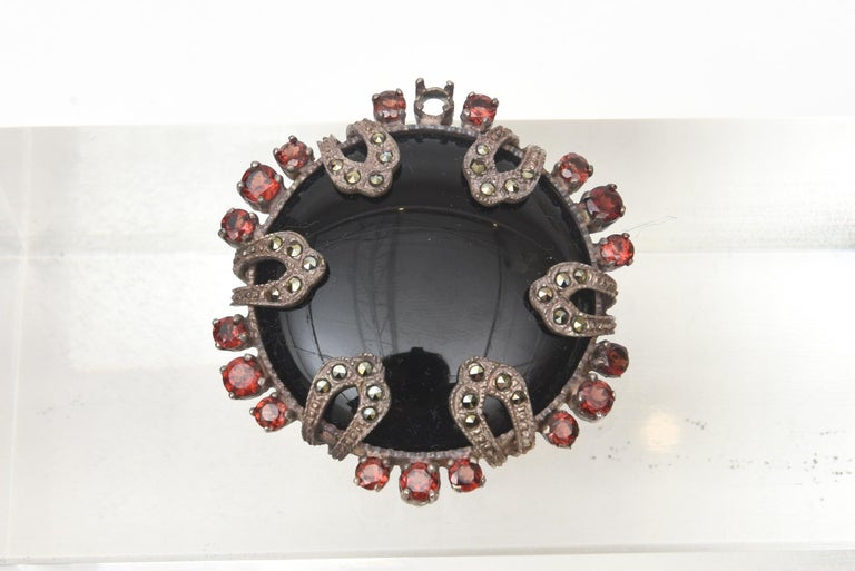 This gorgeous small but stately art deco pin / brooch is black onyx, surrounding garnets, sterling silver and marquisette. It is marked 925 MT. It will adorn any great lapel of a jacket of blouse. it is elegant and timeless. From the 30's. This will