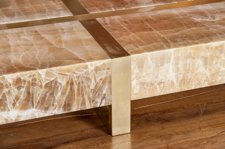 A large polished onyx coffee table with structure in brass. Customizable dimensions. Creation by Studio Glustin.