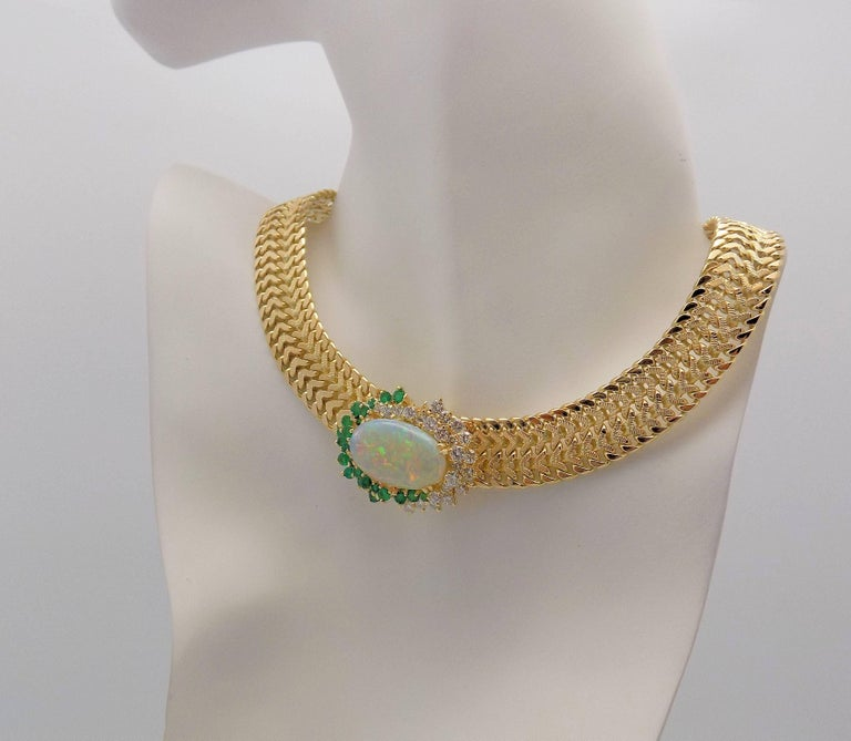 "18 Karat Yellow Gold Necklace 1 Oval Cabochon Cut Opal 6.00 Carat; 24 Round Brilliant Diamonds 2.00 Carat Total Weight SI, H-I; 23 Round Emeralds 1.40 Carat Total Weight; Woven Chain 16 MM; 15"" 84.6 DWT or 131.56 Grams."