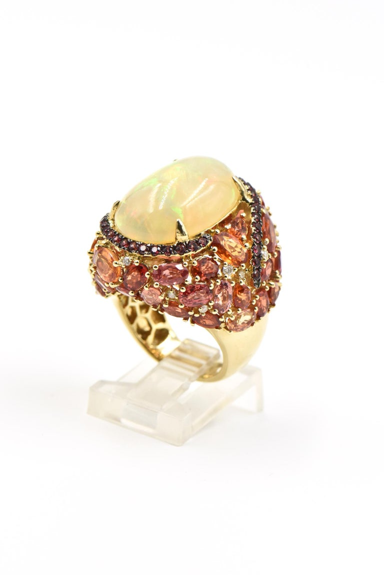 Beautifully made 18k yellow gold cocktail ring featuring a prong set 9.18 carat opal set in a pink sapphire swirl that leads to a cascade of faceted vitrines with .16 carats of diamond accents.  This ring is truly spectacular even the back has a