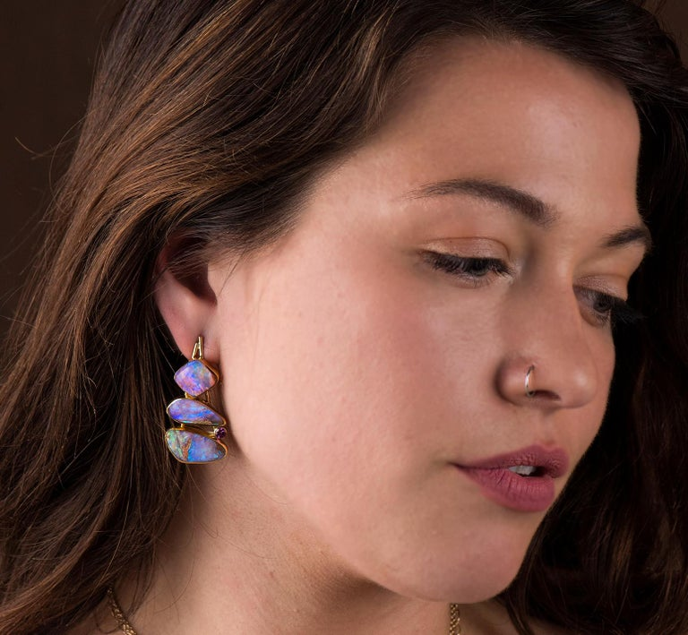 Opal is found in many type of matrix's.  These earrings are opal in petrified wood!  Amazing really.  The color and depth of the opal is lovely, framed in high carat 22k gold with 18k gold accents.  The grape garnet pulls a bit of the purple out of