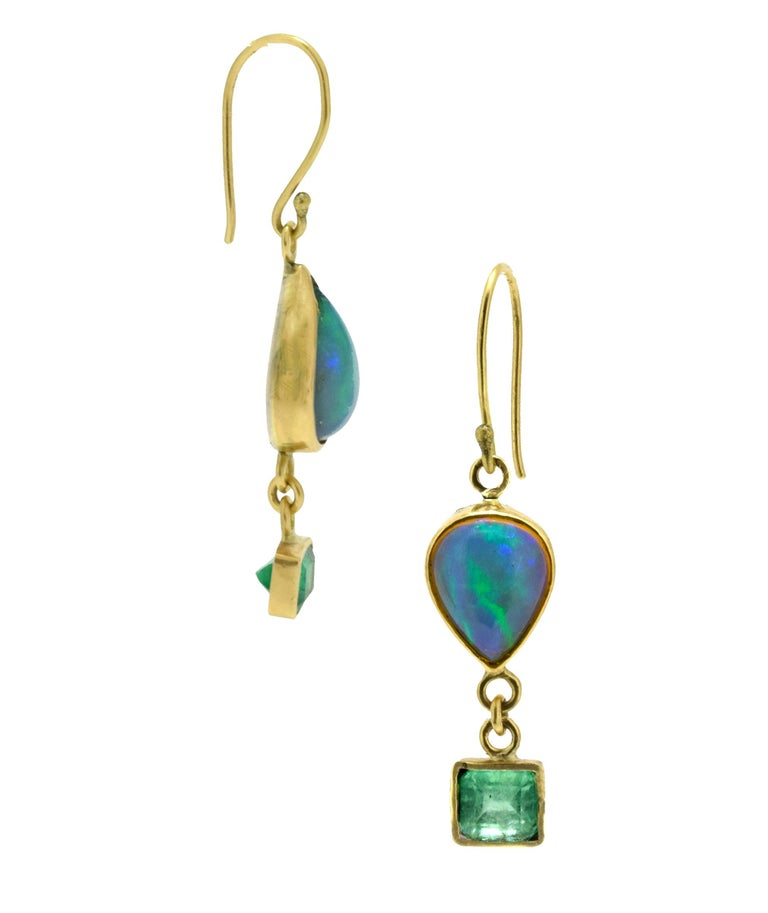 Ethiopian teardrop opals (4.67tcw) are paired with rectangular emeralds (3tcw) in these asymmetrical drop earrings. These opals have a lot of green/blue fire in them that glows when the light hits them. Bezel set in 18k recycled gold with a sterling