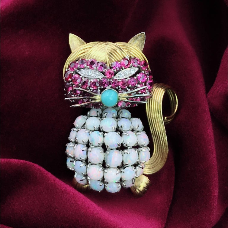 Opal Ruby Diamond and Turquoise Cat Pin. Crafted out of 14K yellow gold, with a belly of round opal cabochons, round-cut rubies on the face, weighing approximately 2.55 carats, round-cut diamonds for the eyes and turquoise for the nose; measures