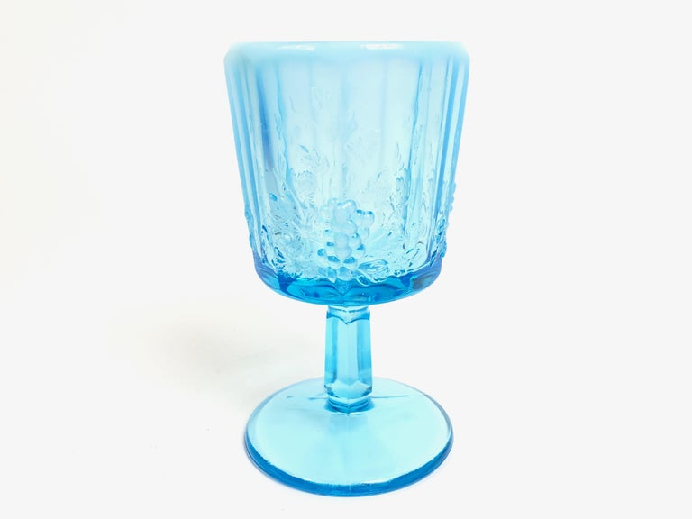 Set of 18 vintage graduated opalescent blue-paneled glass goblets (10 count) with matching sherbets or champagnes (8 count). These opalescent blue paneled glass goblets feature nine panels with three textured grape bunches around the perimeter. The
