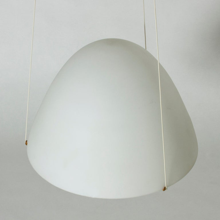 Stunning pendant light by Bertil Brisborg, made from opaline glass with brass details. The large shade is suspended on a slender brass frame whose arms the cords run through. A glass disc discreetly conceals the light source inside. Wonderful