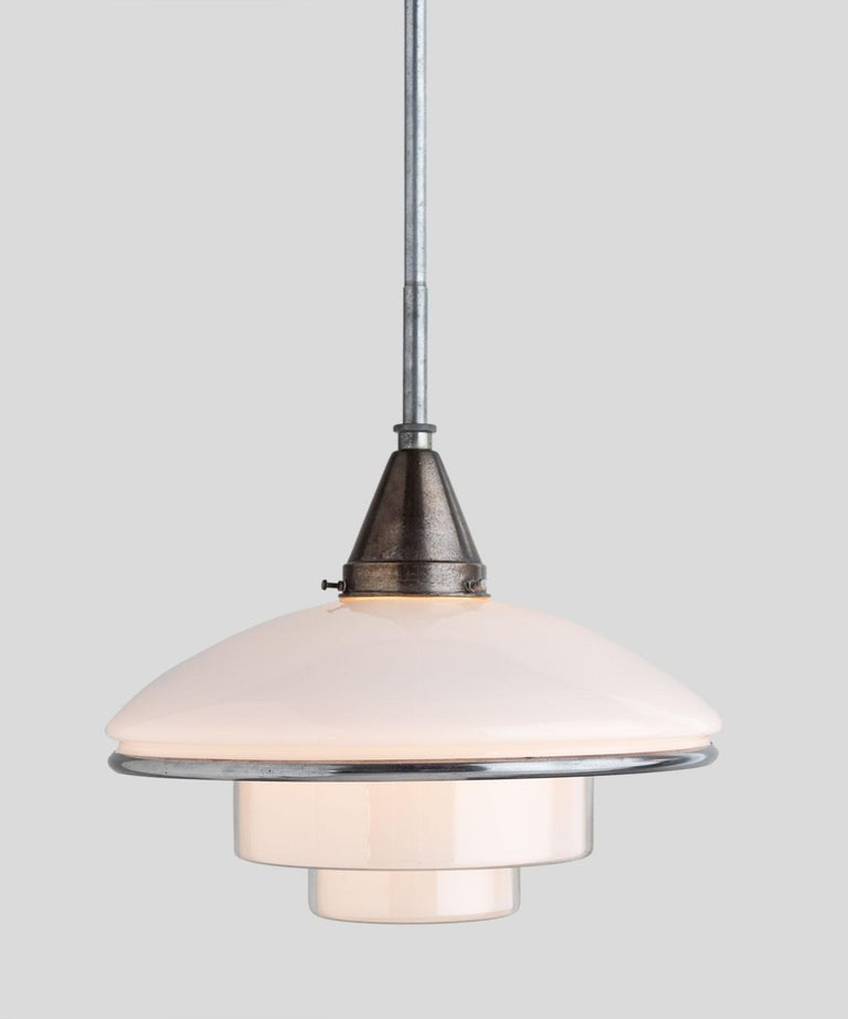 Opaline glass pendant by Otto Müller, circa 1931.  Designed by Otto Müller, manufactured by Sistrah in Germany. Composed of two main glass elements, a white opaline glass dome and an inverted ziggurat shaped opaline glass shade. Chrome-plated belt.